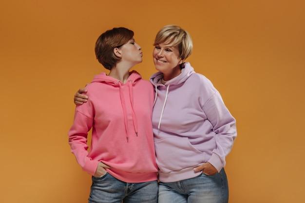 Chica joven y fresca con cabello morena en sudadera rosa y jeans soplando beso y abrazándose con sonriente mujer de cabello rubio.