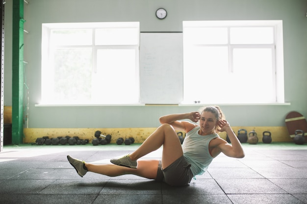 Chica joven y fuerte con una sonrisa haciendo ejercicios para los músculos del estómago, presiona el piso en la espora.