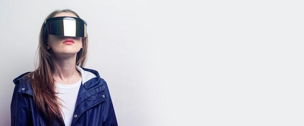 Chica joven con gafas de realidad virtual en una chaqueta azul sobre un fondo claro. bandera.