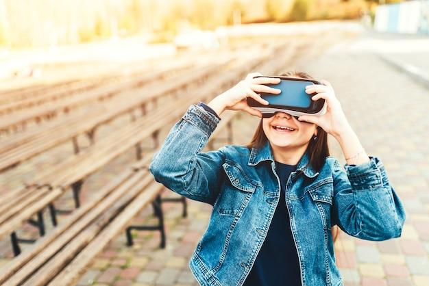 Chica joven en gafas de realidad virtual en el parque