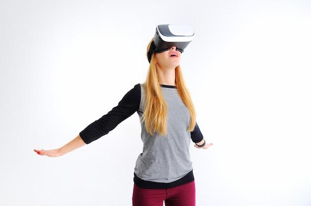 Chica joven con gafas de realidad virtual sobre blanco