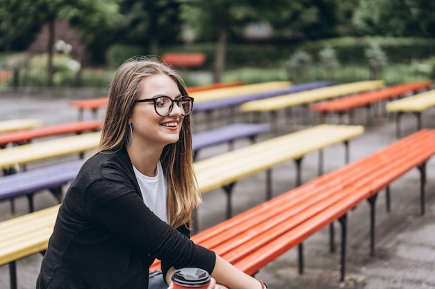 Chica joven con gafas se ve en un teléfono celular. en su segunda mano sostiene una taza de café sentada en un banco del parque. concepto de comunicación y redes sociales.