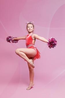 Chica joven gimnasta animadora haciendo un ejercicio