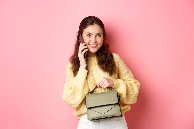 Chica joven glamour sosteniendo su bolso, hablando por teléfono inteligente y sonriendo, teniendo una conversación informal por teléfono, llamando a alguien, de pie sobre una pared rosa