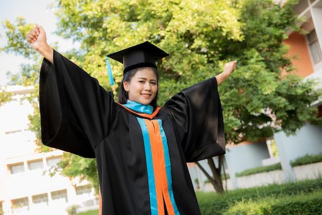 Chica joven graduada que lleva un sombrero negro de la borla.