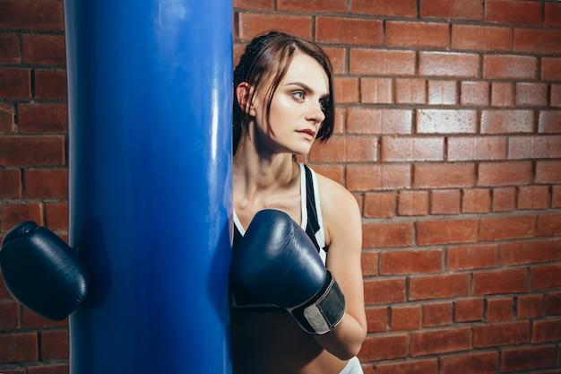 Chica joven en guantes descansando después de un entrenamiento en el gimnasio de boxeo