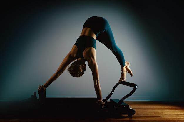 Chica joven haciendo ejercicios de pilates con una cama de reformador. hermoso entrenador de fitness delgado en reformador