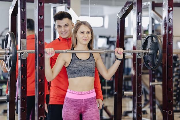 Chica joven haciendo sentadillas con una barra en el gimnasio bajo la supervisión de un entrenador