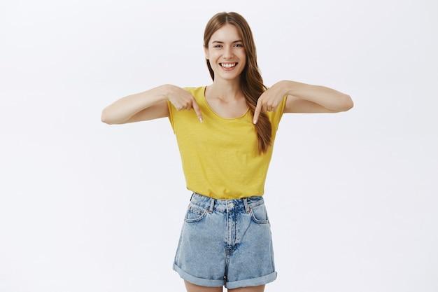 Chica joven hermosa alegre que muestra el anuncio o el logotipo, apuntando hacia abajo