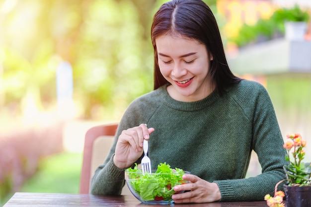 Chica joven hermosa asiática que come el vehículo de la ensalada