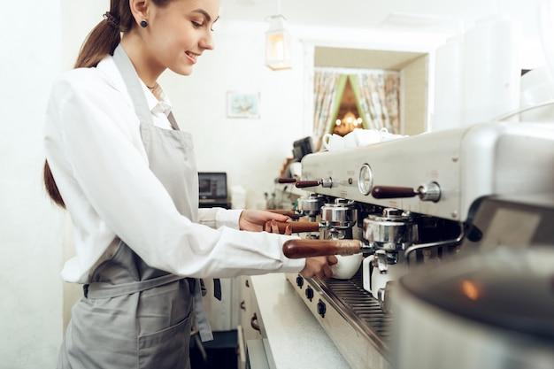 Chica joven hermosa barista que prepara el café