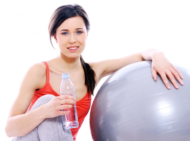 Chica joven y hermosa con una botella de agua mineral.