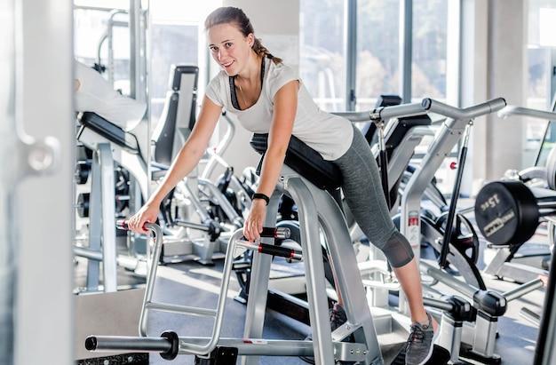 Chica joven hermosa de buen ajuste vestida con ropa deportiva está haciendo ejercicio en el equipamiento deportivo en el moderno gimnasio lleno de luz solar. foto horizontal