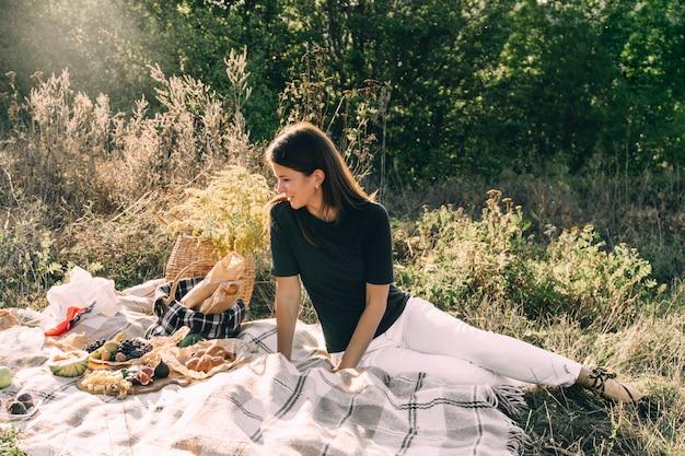 Chica joven hermosa en una comida campestre en un día de verano.