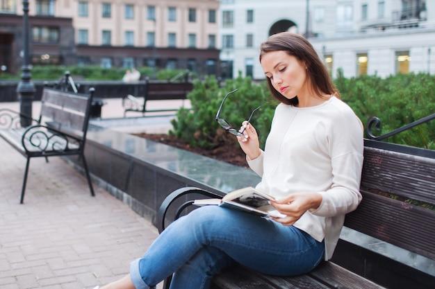 Una chica joven hermosa con el pelo marrón largo que se sienta en un banco con un libro