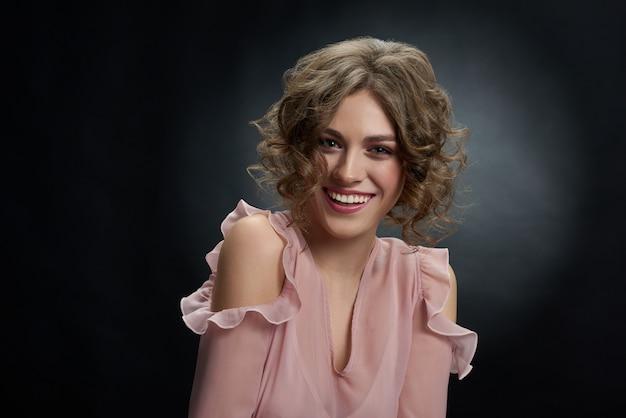 Chica joven hermosa con el pelo marrón rizado que mira la cámara y la sonrisa.