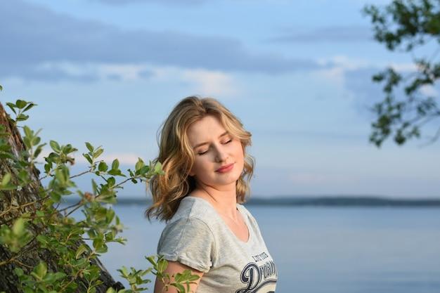 Chica joven hermosa que descansa sobre una tarde del verano en naturaleza y en la ciudad