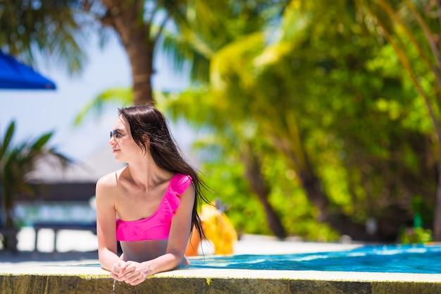 Chica joven hermosa que se relaja en la piscina