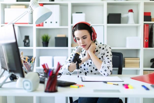 Chica joven hermosa que se sienta en auriculares y con el micrófono en la tabla en oficina y hablar