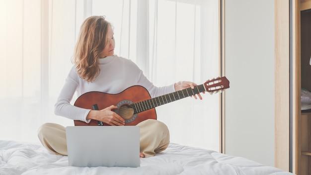Chica joven hermosa que se sienta tocando la guitarra en cama en dormitorio