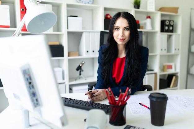 Chica joven hermosa que trabaja con la computadora y documentos en la oficina en la tabla