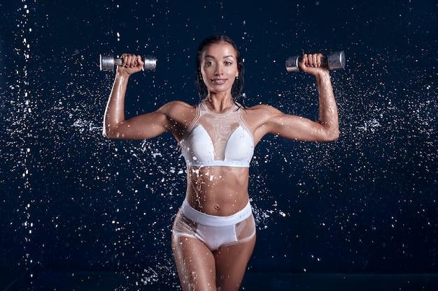 Chica joven hermosa en ropa de deportes en estudio de la aguamarina.