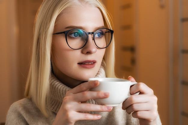 Una chica joven y hermosa, rubia de ojos azules y pestañas largas, con gafas de montura negra