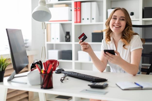 La chica joven hermosa se sienta en la oficina, sostiene una tarjeta de banco y un teléfono en su mano.