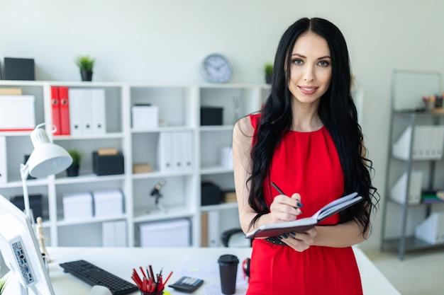 La chica joven hermosa en un traje rojo se está colocando en la oficina y está sosteniendo un cuaderno y un lápiz