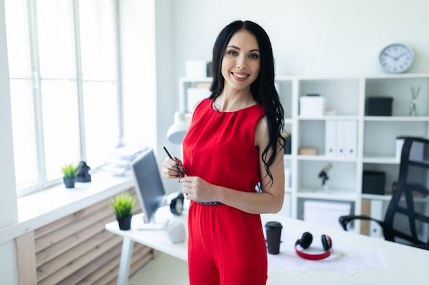 La chica joven hermosa en un traje rojo se está colocando en la oficina y está sosteniendo un lápiz en su mano