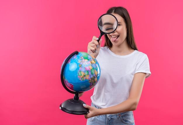 Chica joven hermosa viajera sosteniendo globo mirando a cámara a través de lupa feliz y positivo sacando la lengua