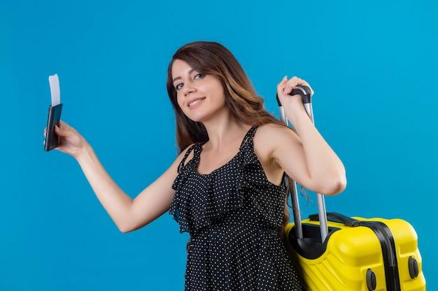 Chica joven hermosa viajera en vestido de lunares con maleta y billetes de avión mirando a cámara con sonrisa segura de pie sobre fondo azul