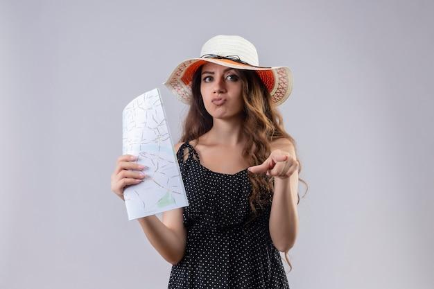 Chica joven hermosa viajera en vestido de lunares en sombrero de verano apuntando con el dedo a la cámara con expresión escéptica en la cara de pie sobre fondo blanco