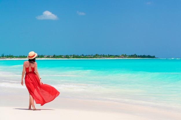 Chica joven en hermoso vestido rojo en la playa
