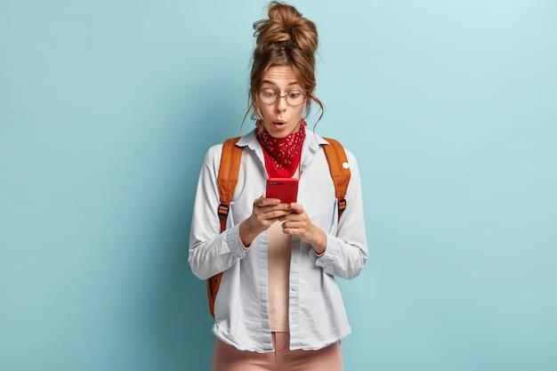 Chica joven inconformista sorprendida mira sorprendentemente al teléfono celular, recibe un mensaje inesperado, lleva una mochila