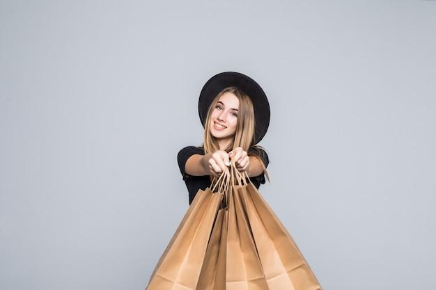 Chica joven inconformista vestida con camiseta negra y pantalones de cuero con bolsas de compras artesanales con asas aisladas en blanco