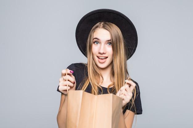 Chica joven inconformista vestida con camiseta negra y pantalones de cuero con bolsas de compras artesanales en blanco con asas aisladas en blanco