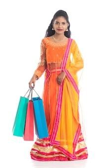 Chica joven india hermosa que sostiene bolsos de compras mientras que lleva ropa étnica tradicional. aislado en una pared blanca