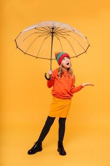 Chica joven integral en suéter y sombrero con paraguas esperando lluvia sobre naranja