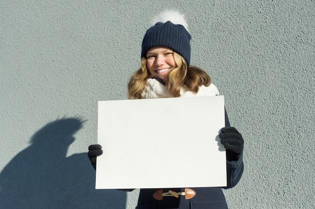 Chica joven en invierno tiene una hoja de papel blanca limpia