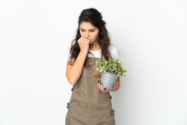 Chica joven jardinero ruso sosteniendo una planta aislada teniendo dudas