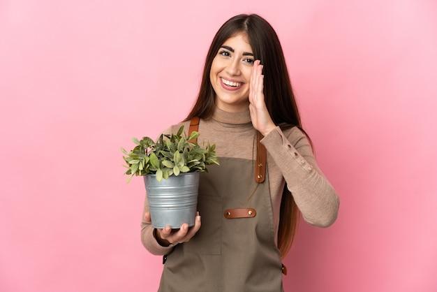 Chica joven jardinero sosteniendo una planta aislada en la pared rosa gritando con la boca abierta
