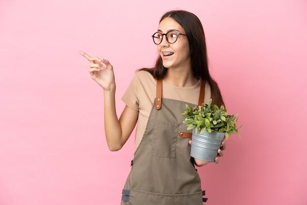 Chica joven jardinero sosteniendo una planta aislada sobre fondo rosa con la intención de darse cuenta de la solución mientras levanta un dedo