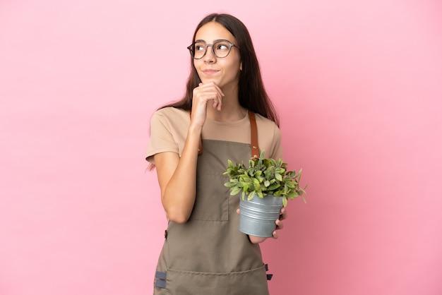 Chica joven jardinero sosteniendo una planta aislada sobre fondo rosa y mirando hacia arriba