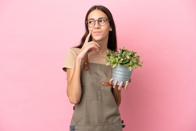 Chica joven jardinero sosteniendo una planta aislada sobre fondo rosa pensando en una idea mientras mira hacia arriba