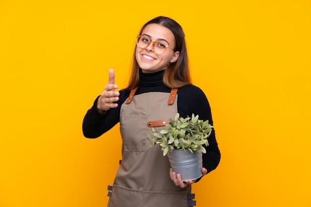 Chica joven jardinero sosteniendo una planta sobre apretón de manos amarillo aislado después de buen trato