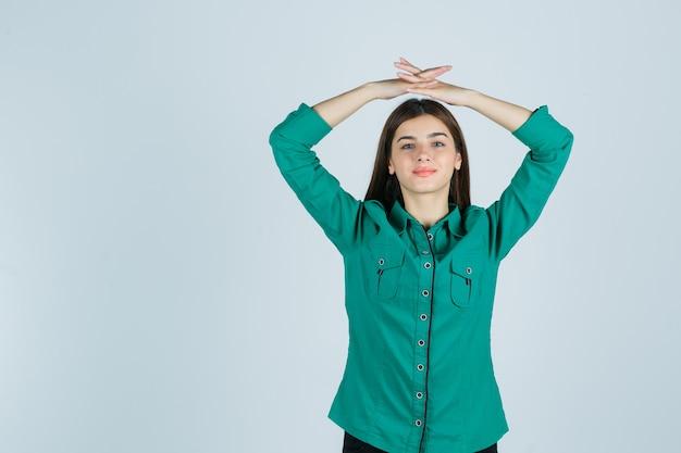 Chica joven juntando las manos por encima de la cabeza mientras posa en blusa verde, pantalón negro y luciendo seductora, vista frontal.