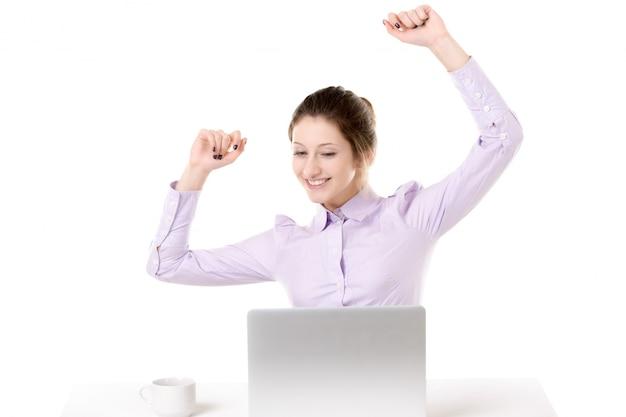 Chica joven levantando los brazos con expresión feliz en frente de la computadora portátil