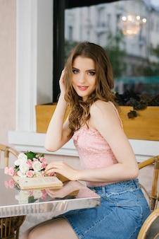 Chica joven linda que se sienta en una tabla en un café del verano de la calle, sosteniendo un libro en sus manos y sonriendo