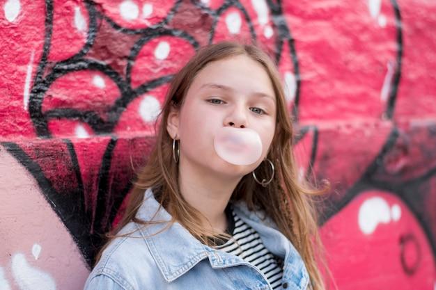 Chica joven linda que sopla el chicle contra la pared de la pintada